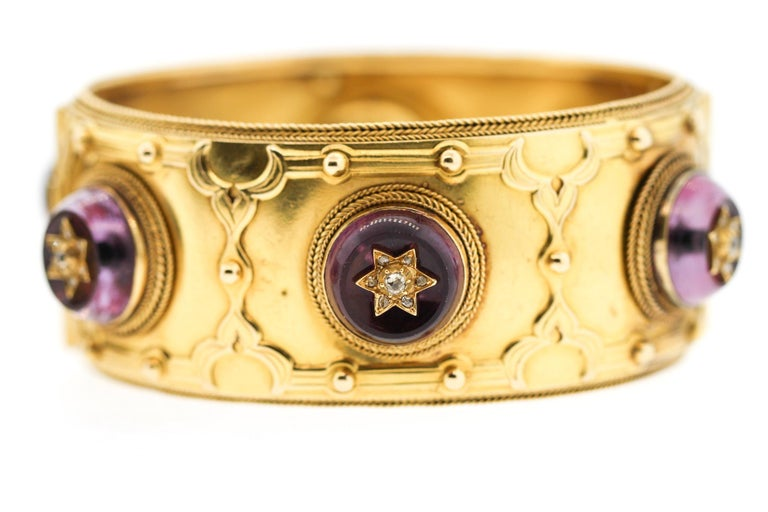 A rare Victorian pair of 18k gold cuffs set with large amethysts that are studded with rose cut diamonds made by Carlo Giuliano around 1860. The cuff bracelets have the makers mark for Giuliano