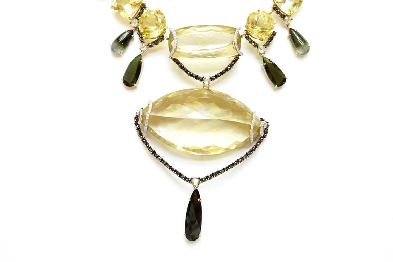 Melanie Necklace An eighteen-karat yellow gold seventeen-inch necklace depicting many cuts and shapes of the gemstone lemon quartz. Beginning from the center is an elongated cushion-shaped lemon quartz, draped with a black diamond-encrusted swag.