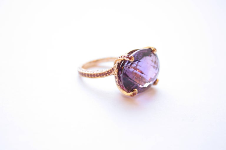 Amethyst & Orange Sapphire Ring An eighteen-karat yellow gold ring showcasing a 25.10 carat ovular faceted amethyst.  The shank has been completely set, on all three sides, with orange sapphires.  Size 7 - adjustable upon request Orange Sapphire