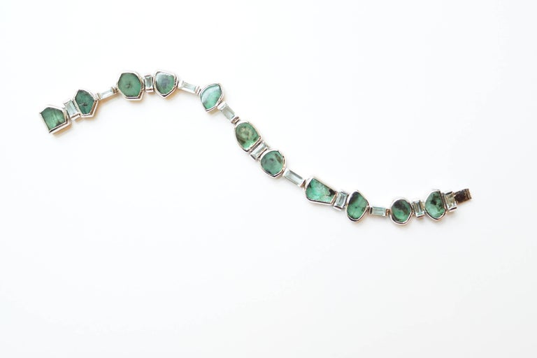 Manza Bracelet A flexible bracelet featuring two different types of emeralds, set entirely in blackened platinum.  The gems have been placed in alternating order of emerald slices and Zambian emerald baguettes of a very unusual mint colour.