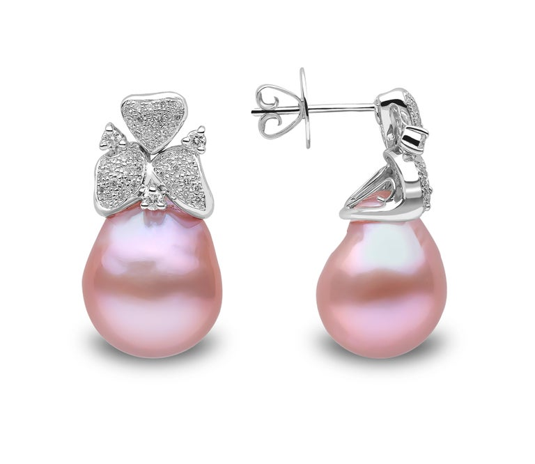 These elegant earrings feature rich pink freshwater pearls beneath a floral arrangement of diamonds. The earrings are set in 18 Karat White Gold to perfectly accentuate the hues of the pearl and sparkle of the diamonds. The unique colour of these