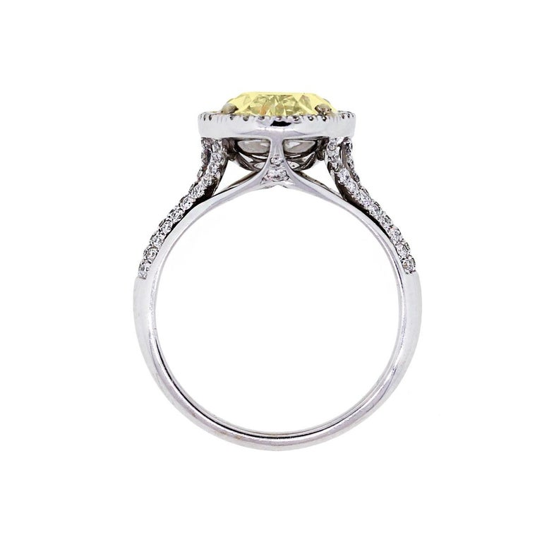 Material: 14k white gold Diamond Details: 6.34ct Fancy Yellow Oval Cut center diamond Side Diamond Details: Approximately 1ctw of round brilliant diamonds. Diamonds are G in color and VS2 in clarity Size: 7.5 (can be sized) Total Weight: 5.9g