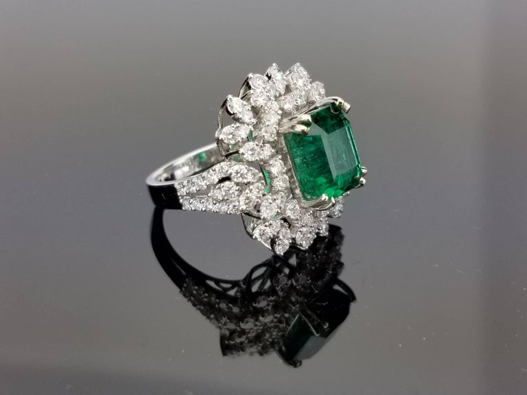 Zambian Emerald Ring surrounded with Brilliant Cut Diamond Cluster on 18K White Gold hoop  Center Stone Details:  Stone: Zambian Emerald Cut: Emerald Cut Weight: 4.81 carat  Diamond Details:  Cut: Brilliant (round) Total Carat Weight: 1.96 carat