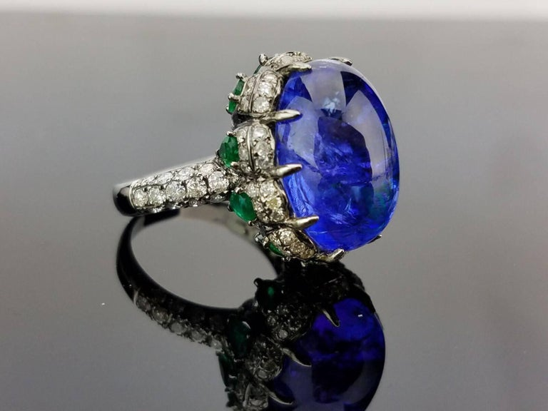 A statement cabochon Tanzanite, Emerald and Diamond cocktail ring - all set in rhodium polished 18K Gold.  Stone Details:  Stone: Tanzanite, Oval Cabochon, 16.70 carat Stone: Emerald, Pear Shape, 1.40 carat  Diamond Details: Cut: Brilliant Total