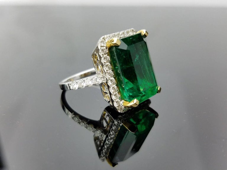 Beautiful and Lustrous, High Quality Zambian Emerald Cocktail Ring outlined with Diamond, all set in 18 White Gold and Yellow Gold prongs.   Stone Details:   Stone: Zambian Emerald Cut: Emerald Cut Carat Weight: 15.19 carat  Diamond Details: Cut: