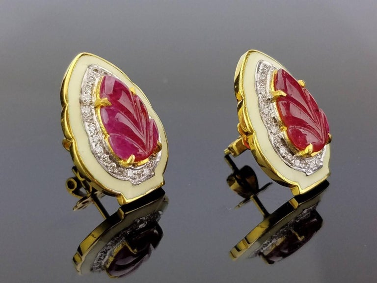 A unique pair of stud earrings, with leaf-shaped carved ruby and white diamonds, outlined with enamel. All set in 18K yellow gold.   Ruby Weight: 5.23 carats Diamond Weight: 0.49 carats (VS/SI , H/I)  Gold Weight: 9.22 grams