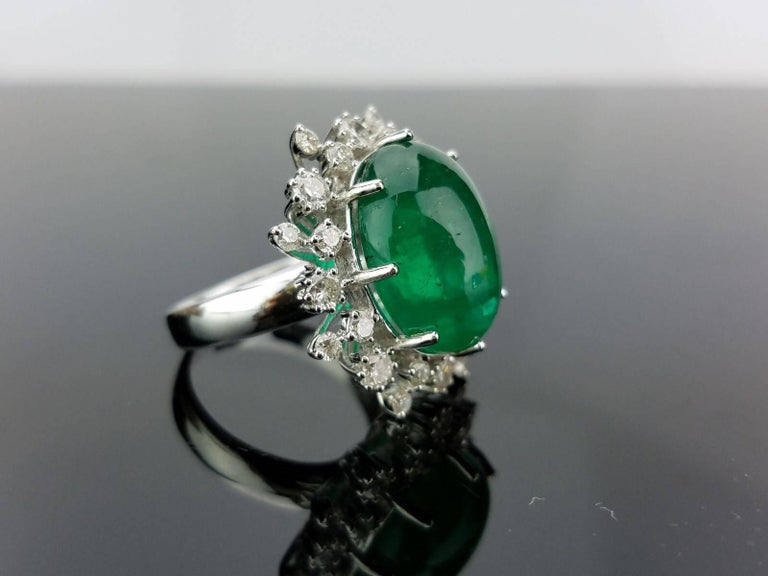 An elegant cocktail ring using a beautiful Emerald Cabochon centre stone surrounded with White Diamond, all set in 18K white gold.   Stone Details:  Stone: Emerald Carat Weight: (approximately) 12 Carats  Diamond Details:  Total Carat Weight: 1.16