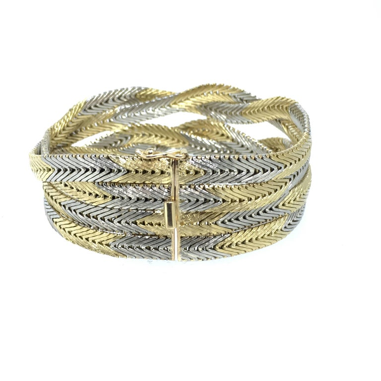 This Braided white and yellow gold bracelet has a nice weighty feel and made in 18K gold with a total weight of 76,8 grams.  The Italian design and the specific surface treatment give this bracelet this special occurrence. Made out of 4 strings