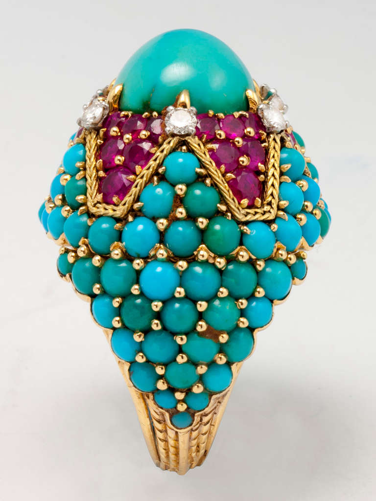18 karat yellow gold ring, centering one oval cabochon cut turquoise, six round brilliant cut diamonds, and 36 mixed- cut rubies, and numerous round cabochon turquoise. Hand inscribed MARCHAK PARIS 33396.