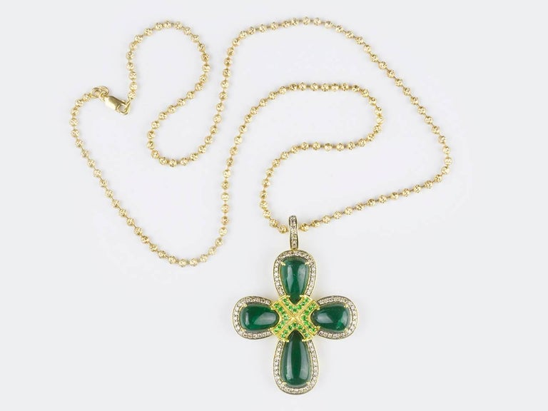 Pendant features 4 pear-shaped emerald cabochon emeralds in colored diamond-set frames and round garnets with blackened gold accents. Signed WINC. (Robert Wander). Cross is suspended from gold ball-link chain.