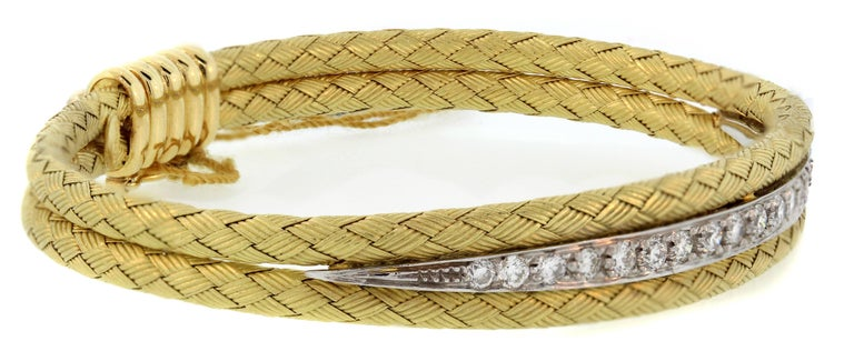 18K Yellow and White Gold Bracelet with Diamonds   0.90ct. Diamonds cover mid section of bracelet surrounded by gorgeous textured design work.  Bracelet is 0.35 inch wide and 7 inches in length.  Push open clasp along with safety used to lock and