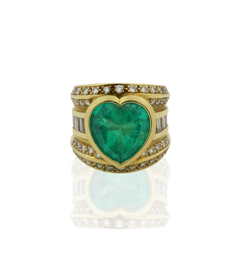 18K Yellow Gold Ring with Heart Shape Emerald center and round, baguette diamonds  Heart Shape Emerald is incredible in color, quality. Apprx. 10 carat. 13mm x 12.55 dimensions. Emerald does not have certification. Origin is unknown.  This estate