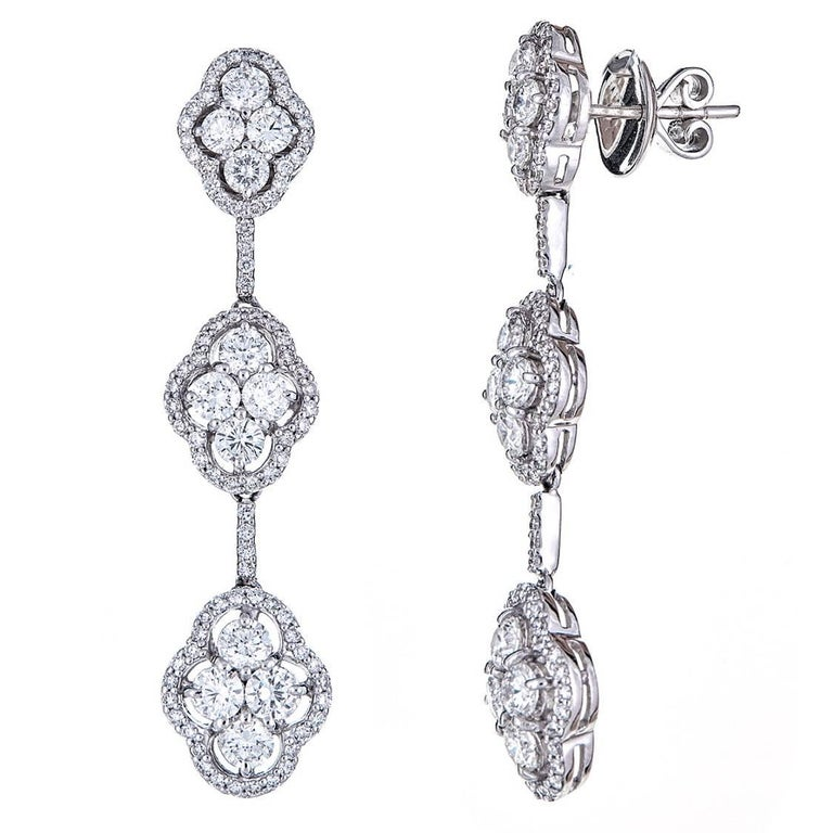 Three delicately tiered, diamond cluster earrings with 4.70 carats of round white Diamonds. Set in 18K White Gold, each tier holds four larger diamond stones surrounded by pave diamonds for effortless, minimalistic glamour.   Features: Post
