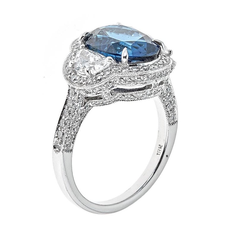 An elegant and romantic cocktail or engagement ring set in 18K White Gold. With an air of vintage sophistication this piece features a gorgeous 5.22 carat center Blue Sapphire. The Sapphire is flanked by 0.69 carats of white, half-moon Diamonds with
