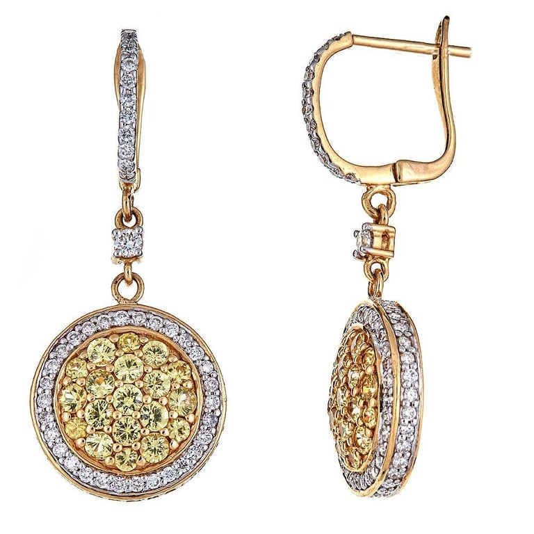 Featuring 1.80 carats of vivid Yellow Sapphires surrounded by numerous brilliant Diamonds, these drop earrings are perfect go-to pieces for all occasions. Set in 18K Yellow Gold, each circle of bold center stones is haloed by a ring of white