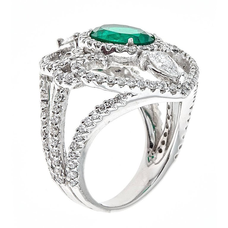 Featuring a magnificent 1.66 carat center oval Emerald, this exquisitely designed cocktail ring is set in 18K White Gold. Complimenting the vibrant green emerald are flourishes of round and pear shaped white Diamonds. With an intricately designed