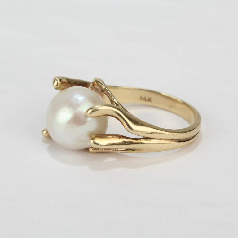 A fine, modernist 14k yellow gold and baroque pearl cocktail ring from the mid-20th century.  Features a large baroque pearl in an organic, pronged setting.  Interior of shank stamped: 14K   Overall Width: ca. 3/4 in. Ring size: 6.5  Pearl size: