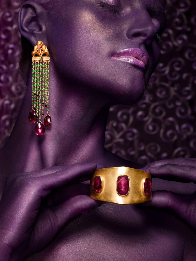 A pair of spectacular and unique, hand crafted 18 karat gold precious stone earrings. Dark red Tourmaline drops are suspended by vibrant green tsavorite beads. Small onyx beads are playfully dispersed among the tsavorite which are held by an 18