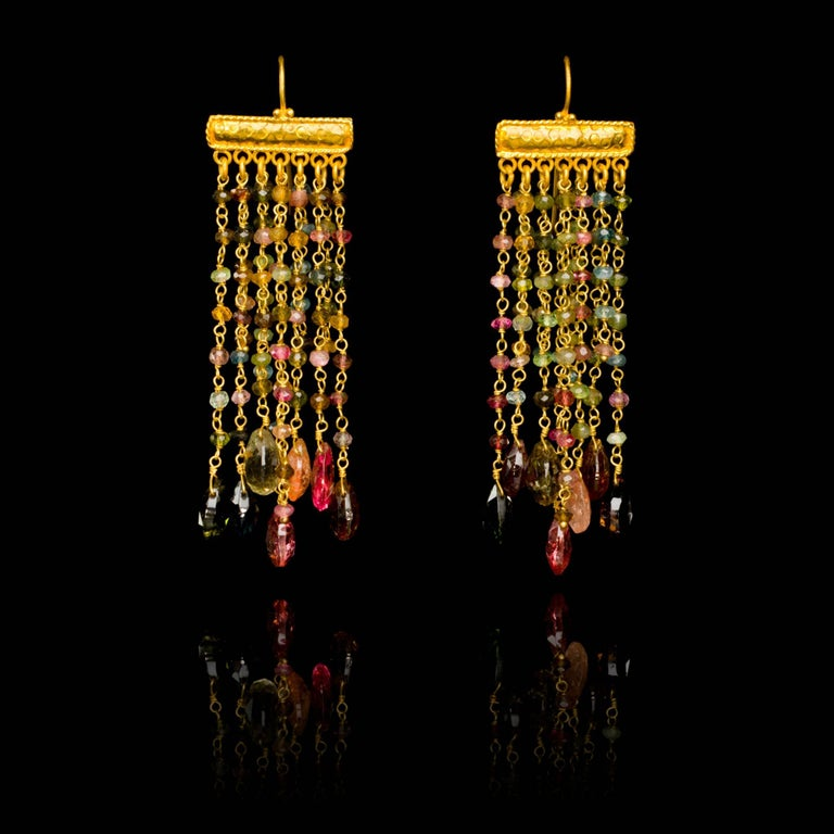 Hand embossed 18 karat gold chandelier earrings with tourmaline beads and briolettes. Due to the hand crafted nature of these jewels, slight asymmetry may occur. The earrings are 8cm, 3.13in long and 2cm, 0.75in wide. The weight of each earring is