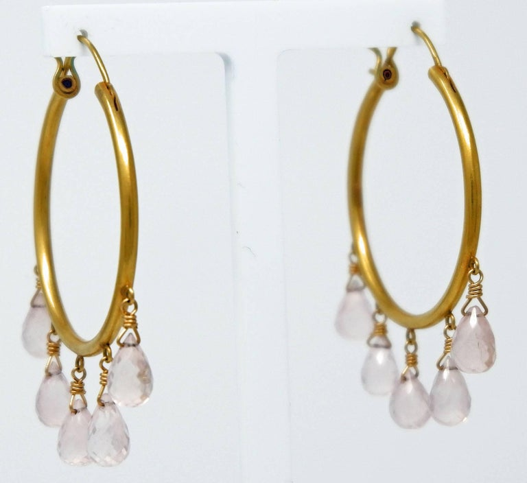 A pair of 18 karat brushed gold earrings with delicate rose quartz briolettes.  Dazzle with these large hoop earrings which look stunning day as well as night. The delicate rose quartz briolettes are translucent and slightly milky in colour adding a