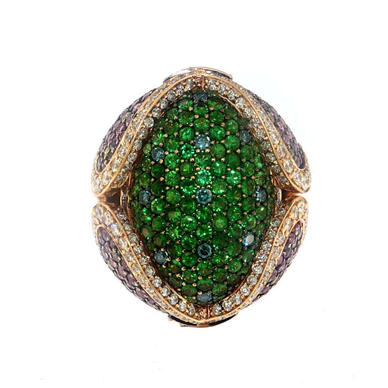 This bombe cocktail ring is a triumph of colorful precious gemstones featuring 2.92 Carats of Tsavorite Garnet at the dome with 3.69 Carats of Pink Sapphires, 1.60 Carats of White Diamonds, and 0.33 Carats of treated Blue Diamonds set on a pave-set
