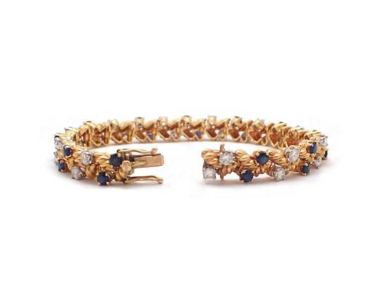 This unique and intricate bracelet features 22 diamonds and 22 blue sapphires for over 5ct in total weight. This bracelet makes a great compliment to any sapphire or gold jewelry. G-H color, VS clarity.