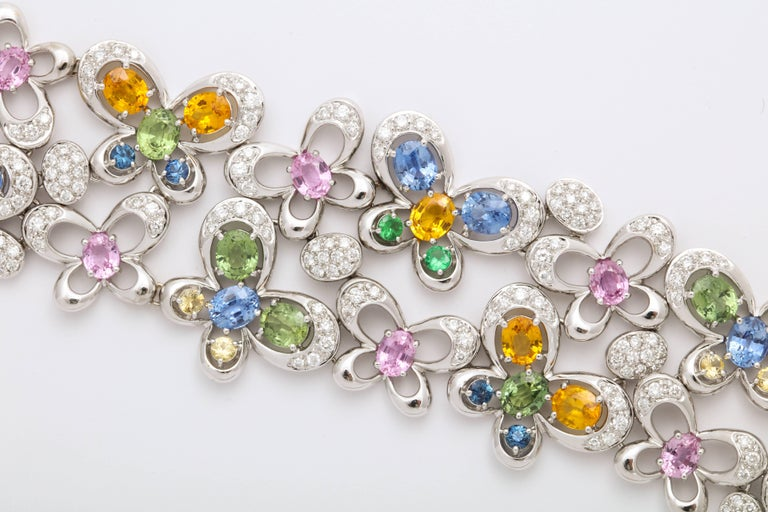 Festive 18 Karat White Gold articulating strap bracelet mounted with oval faceted blue and green sapphires: 2.96 carats; and pink and yellow sapphires: 7.73 carats, in the form of butterfly motifs, with staggered tsavorites (green garnets),