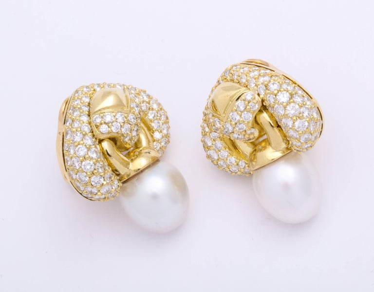 Contemporary and very chic day-into-night 18 Karat yellow gold earrings decorated with round brilliant cut diamonds: 4.84 carats, suspending gently articulating oval shaped silvery-moon color south sea pearls: 12.5 x 11.5 mm. French clip