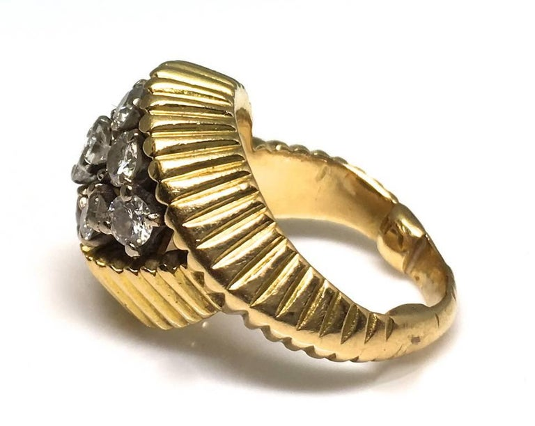 A Cartier 1960's gold and diamond ring.  A sweet little ring made of carved and fluted 18ct gold. It comprises of a cluster of diamonds weighing approximately 0.90pts. The ring is signed Cartier under the bezel. Size US 3 1/4.