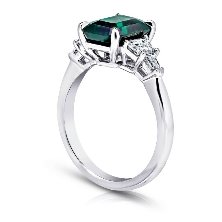 This meticulously crafted ring has a center Emerald Cut Green Sapphire weighing 3.83 carats with two trappazoid and two bullet shape diamonds (F+ VS1+) weighing .68 carats. All set in platinum ring. The center stone is total clean and has a great