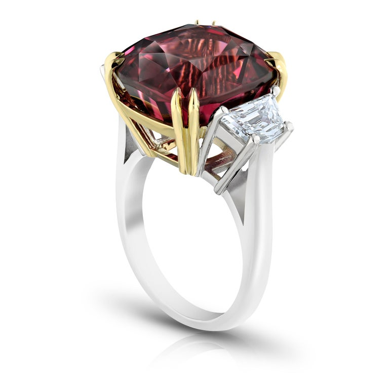 18.37 carat cushion red spinel with two trapezoid  shaped diamonds weighing 1.35 carats set in a platinum and 18k yellow gold ring.