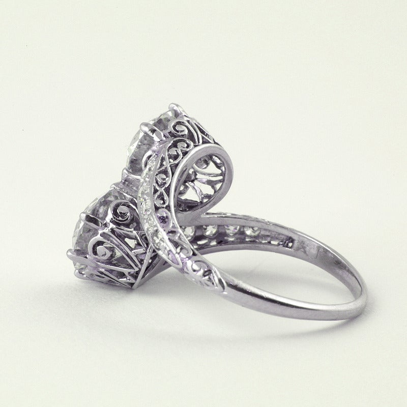 An American early Art Deco platinum ring with diamonds. The ring has two round old European-cut diamonds, one weighs 2.11 carats with an SI-1 clarity and an F color grade. The other diamond weighs 2.01 carats with a SI-1 clarity and an E color
