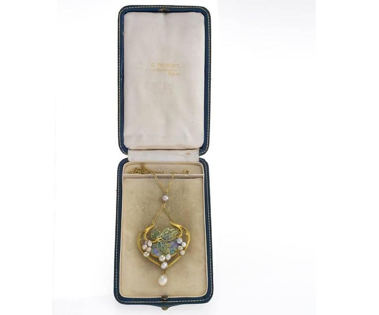A French Art Nouveau gold and plique-à-jour enamel pendant with opals and freshwater and natural pearls by Georges Fouquet. The pendant has 11 opals, and 13 freshwater pearls and one natural saltwater pearl drop.  The pendant is designed in a