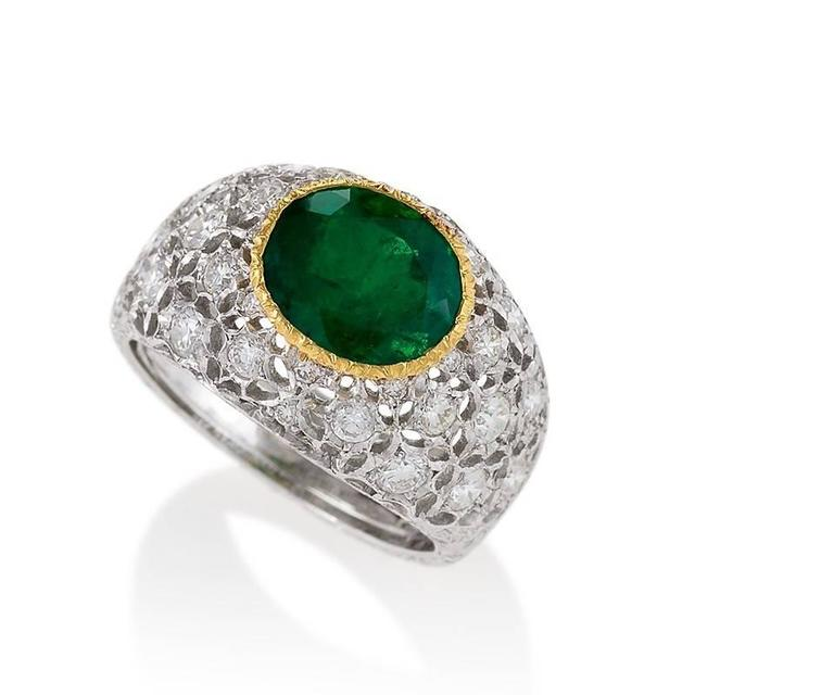 An Italian Estate 18 karat white and yellow gold ring with emerald and diamonds by Buccellati. The ring has an oval-cut Colombian emerald with an approximate total weight of 2.19 carats, and 30 round-cut diamonds with an approximate total weight of