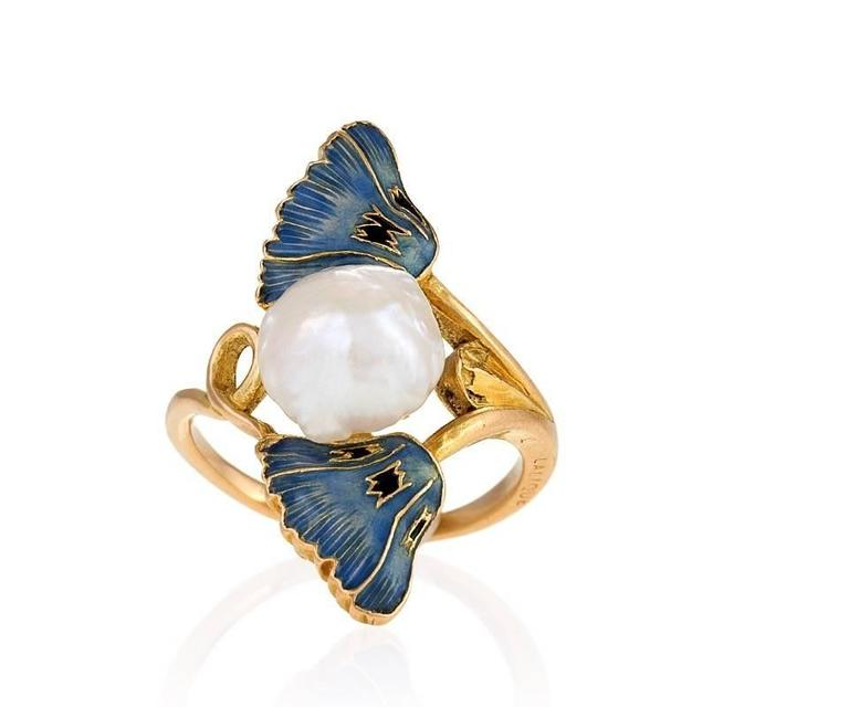 """A French Art Nouveau 18 karat gold, enamel, and pearl ring by René Lalique. The ring has a freshwater baroque pearl measuring approximately 8.85 x 9.01 x 6.5 mm. and two enamel poppies. Circa 1900. Signed, """"Lalique"""".  Pictured in René"""