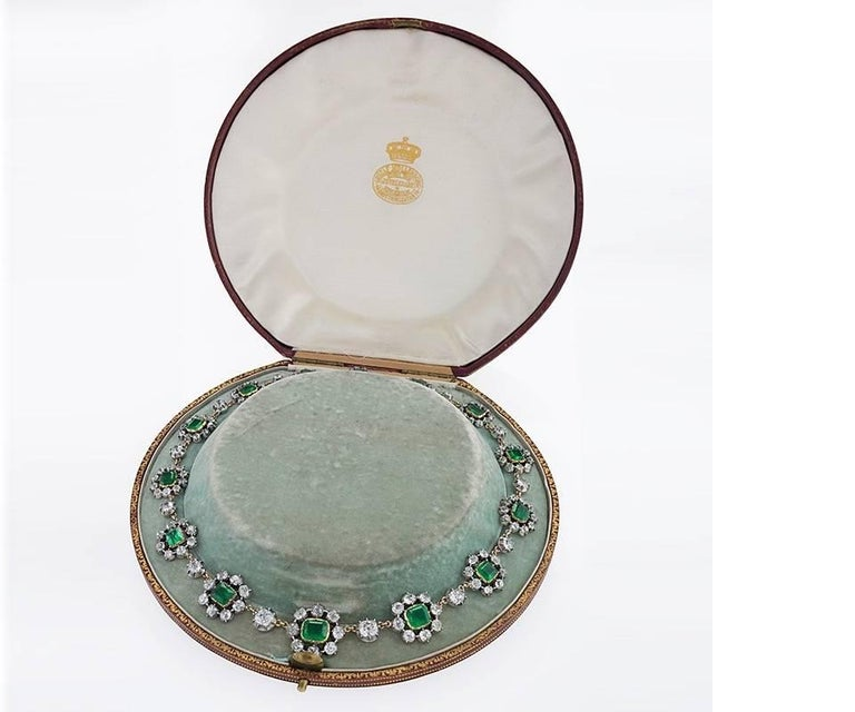 An English antique 15 karat gold and silver necklace with fourteen emerald and diamond clusters. The necklace has 14 antique-cut emeralds with an approximate total weight of 20.50 carats including the center emerald with an approximate weight of