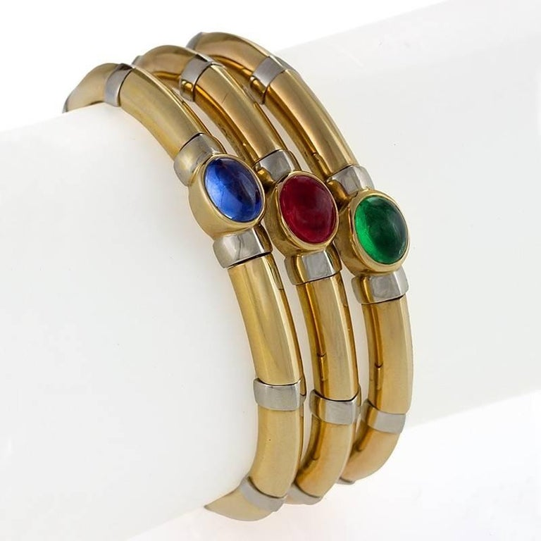 An Italian 18 karat polished white and yellow gold bangle bracelet with sapphire, ruby and emerald by Bulgari. The open back flexible bracelet has 1 cabochon sapphire with an approximate total weight of 2.83 carats, 1 cabochon ruby with an