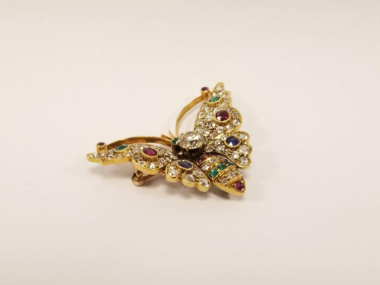 An Antique 18 karat gold butterfly brooch with diamonds,  emeralds, rubies and sapphires. The dimensional butterfly brooch centers on an old European-cut diamond with an approximate weight of 1.00 carat. The brooch has an additional 82 Old