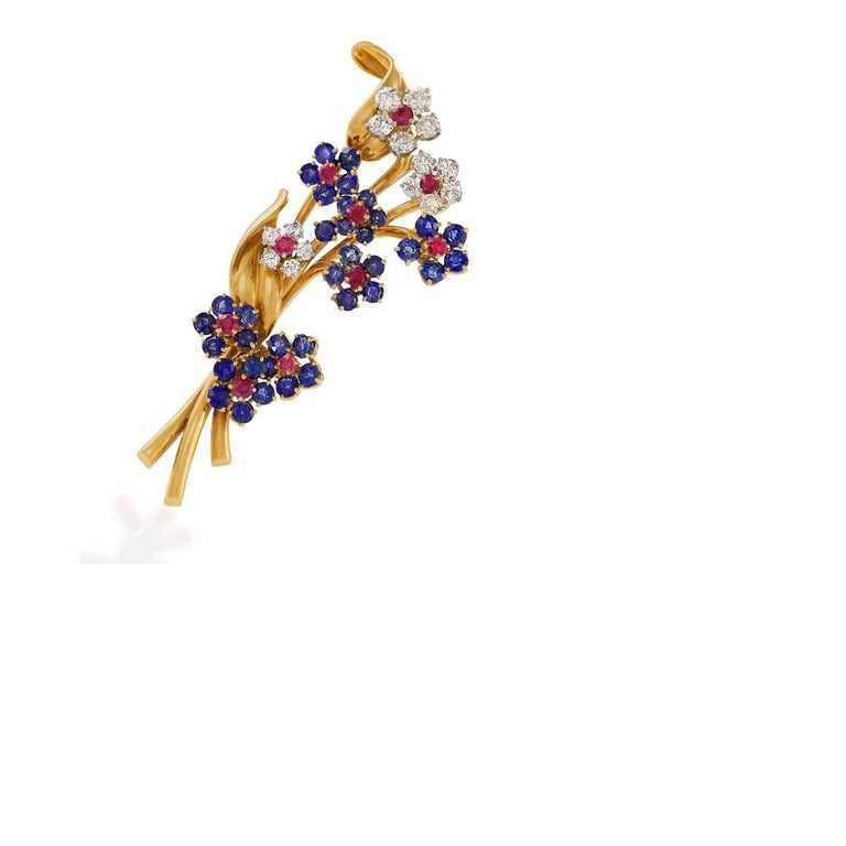 A Mid-20th Century 18 karat gold 'Hawaii' brooch with diamonds, rubies and sapphires by Van Cleef & Arpels. The brooch has 15 round diamonds with an approximate total weight of 1.35 carats, 10 round rubies with an approximate total weight of 1.00