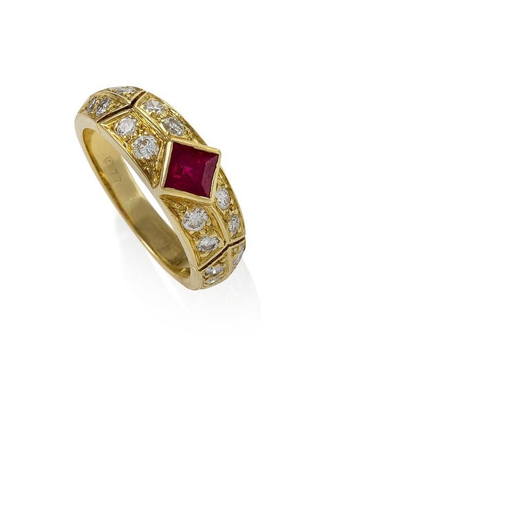 A French 18 karat gold ring with rubies and diamonds by Van Cleef & Arpels. The ring centers on a square-cut ruby with an approximate weight of 1.40 carats, and 16 round brilliant-cut diamonds with an approximate total weight of .64 carats.  Circa