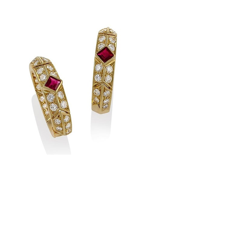 A pair of French 18 karat gold hoop earrings with rubies and diamonds by Van Cleef & Arpels. The hoop earrings have 2 square cut rubes with an approximate total weight of .80 carats, and 60 round cut diamonds with an approximate total weight of 1.40