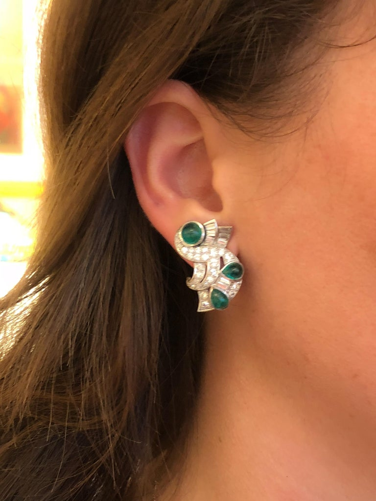 A pair of Retro platinum earrings with diamonds and emeralds. The earrings have 50 round-cut diamonds with an approximate total weight of 2.70 carats, and 16 baguette cut diamonds with an approximate total weight of 1.60 carats. The total