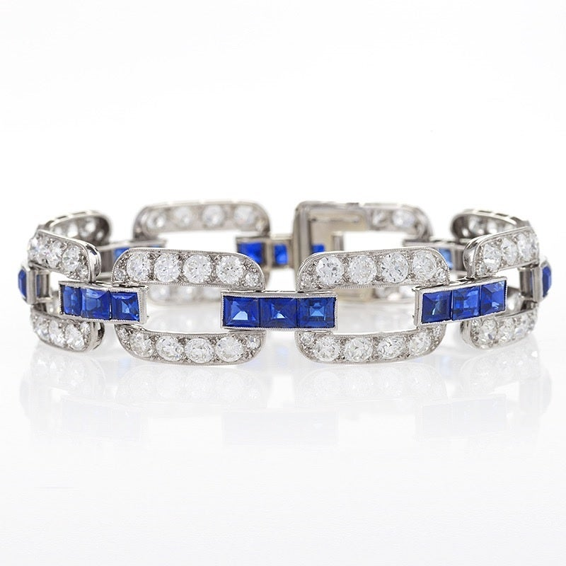 A French Art Deco 18-karat gold and platinum bracelet with blue sapphires and diamonds. The bracelet has 8 open link sections with 64 old European-cut diamonds with an approximate total weight of 9.60 carats, and 32 single-cut diamonds with an