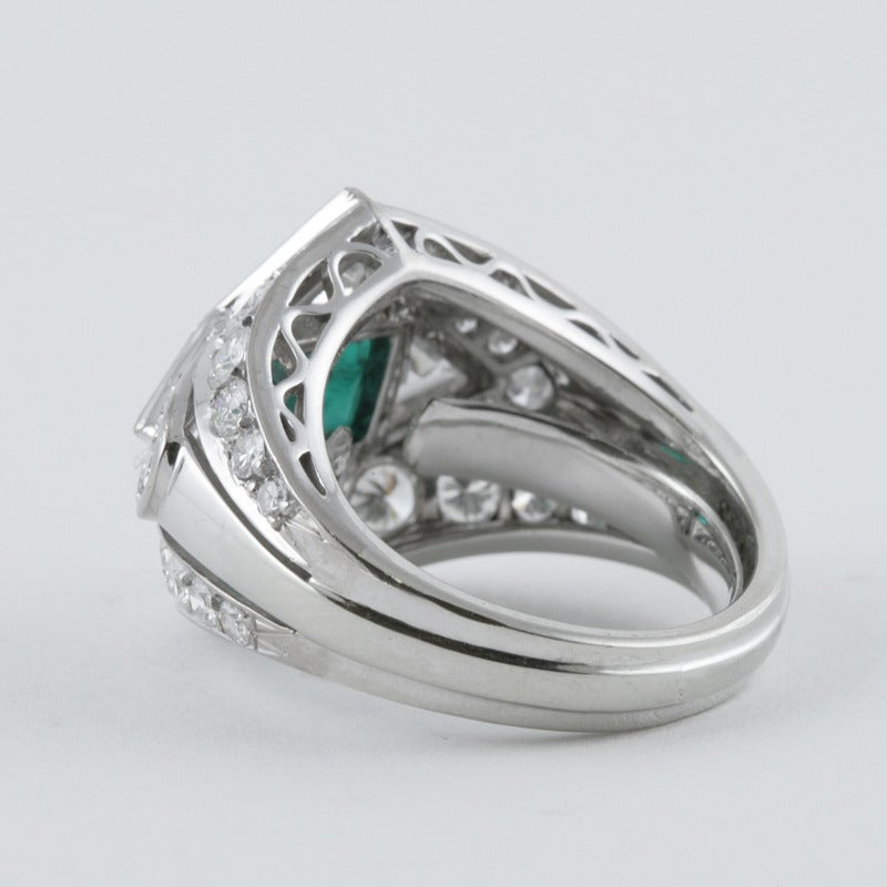 A Mid-20th Century platinum ring with emerald and diamonds. The ring has a rectangular-cut emerald with an approximate total weight of 1.15 carats, 34 round diamonds with an approximate total weight of 2.40 carats, G/H color, VS/SI clarity, and 4