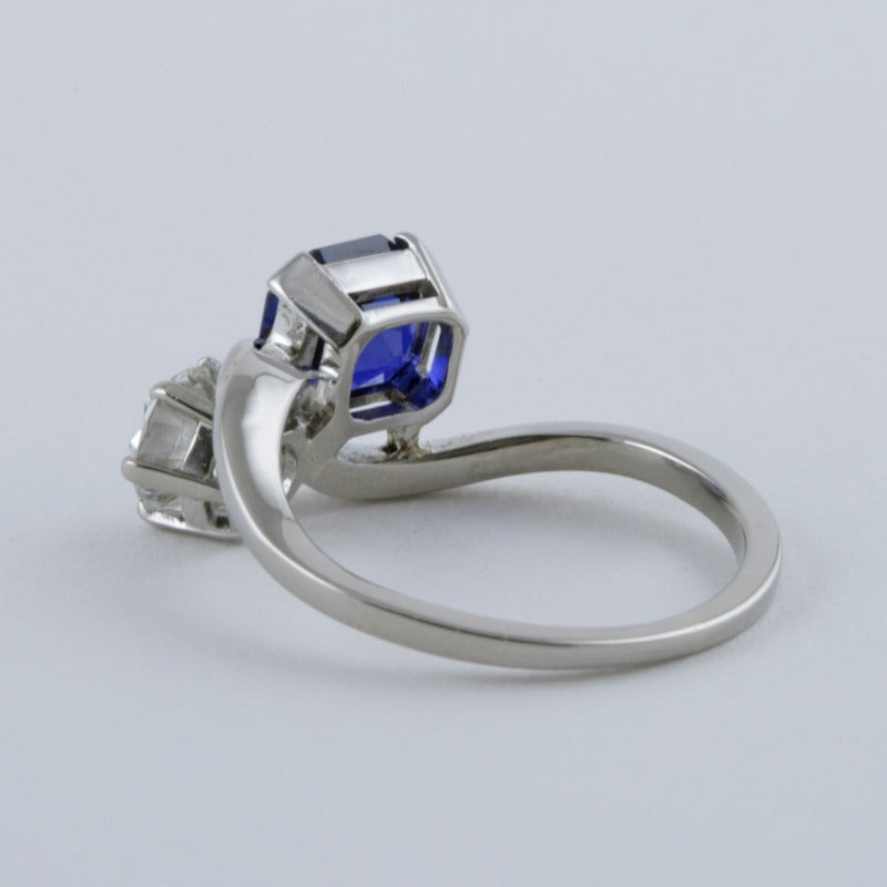 A Mid-20th Century platinum, diamond and blue sapphire moi et toi ring. The classic crossover ring has a round-cut diamond with an approximate weight of .75 carat, I/J color, VS clarity, and a rectangular-cut sapphire with an approximate weight of
