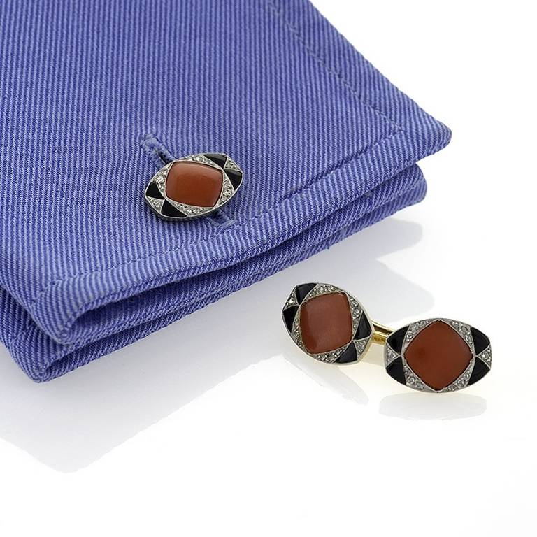 A pair of French Art Deco platinum and 18 karat gold cuff links with diamond, onyx and coral. The cuff links have 56 rose-cut diamonds with an approximate total weight of .40 carats, and polished coral and onyx stones.  Double sided. Circa