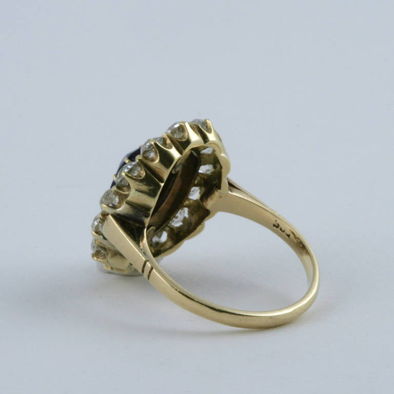 An English Antique 15 karat gold/silver ring with sapphires and diamonds. The ring has oval-cut sapphires with an approximate total weight of .95 carats, 14 old mine-cut diamonds with an approximate total weight of 1.40 carats, and 19 rose-cut