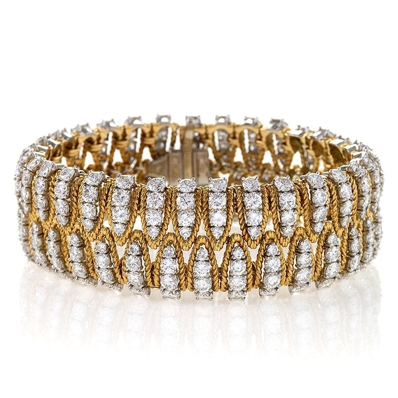 The alternating diamond arches of this flexible mid-20th century bracelet come together to clasp the wrist in a seemingly endless embrace. The sumptuous gold and platinum design and construction of this flexible bracelet fascinates with rhythmic