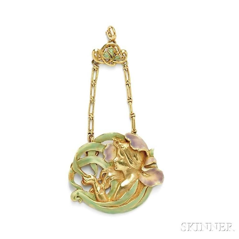 A French Art Nouveau 18 karat gold and enamel pendant by André Rambour. The pendant is designed as a maiden within an enamel iris which is suspended by fancy link chain and enameled foliate top. French control and maker's marks. Circa