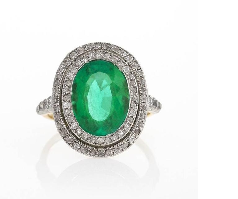 This antique Edwardian gold-shanked ring is set with a four-and-a-half carat oval-cut emerald, exhibiting the classic slightly bluish-green that signifies its rare and desirable Colombian origin. Encircled by a double line of fiery old mine-cut